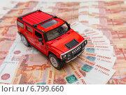 Купить «Красный автомобиль на фоне из пятитысячных купюр», фото № 6799660, снято 9 декабря 2014 г. (c) Джигарян Дмитрий / Фотобанк Лори
