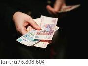 Купить «Российские деньги в руках на черном фоне», фото № 6808604, снято 16 декабря 2014 г. (c) Pavel Ivanov / Фотобанк Лори