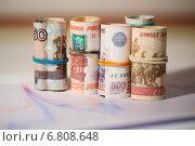 Купить «Рубли в рулонах на фоне графиков», фото № 6808648, снято 16 декабря 2014 г. (c) Pavel Ivanov / Фотобанк Лори