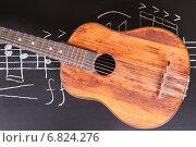 Купить «Гитара на доске с музыкальными нотами», фото № 6824276, снято 11 ноября 2014 г. (c) Сергей Лабутин / Фотобанк Лори