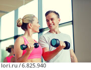 Купить «smiling young woman with personal trainer in gym», фото № 6825940, снято 29 июня 2014 г. (c) Syda Productions / Фотобанк Лори
