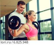 Купить «smiling man and woman with barbell in gym», фото № 6825948, снято 29 июня 2014 г. (c) Syda Productions / Фотобанк Лори