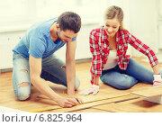 Купить «smiling couple measuring wood flooring», фото № 6825964, снято 26 января 2014 г. (c) Syda Productions / Фотобанк Лори