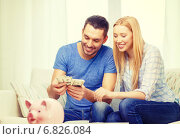 smiling couple counting money at home. Стоковое фото, фотограф Syda Productions / Фотобанк Лори
