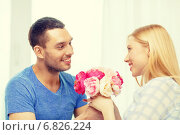Купить «smiling man giving girfriens flowers at home», фото № 6826224, снято 9 февраля 2014 г. (c) Syda Productions / Фотобанк Лори