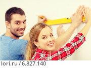 Купить «couple building using spirit level to measure», фото № 6827140, снято 26 января 2014 г. (c) Syda Productions / Фотобанк Лори