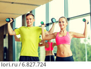 Купить «smiling man and woman with dumbbells in gym», фото № 6827724, снято 29 июня 2014 г. (c) Syda Productions / Фотобанк Лори
