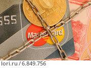 Купить «Блокировка банковских карт MasterCard. Кредитная карта перевязанная цепью», эксклюзивное фото № 6849756, снято 29 декабря 2014 г. (c) Юрий Морозов / Фотобанк Лори