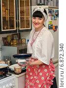 Купить «Радостная женщина средних лет готовит еду на кухне», эксклюзивное фото № 6872340, снято 7 января 2015 г. (c) Игорь Низов / Фотобанк Лори