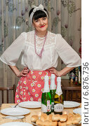 Купить «Женщина-брюнетка средних лет стоит перед накрытым столом, поставив руки на пояс», эксклюзивное фото № 6876736, снято 7 января 2015 г. (c) Игорь Низов / Фотобанк Лори