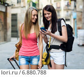 Two women smiling with luggage and using the map. Стоковое фото, фотограф Яков Филимонов / Фотобанк Лори