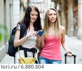 Two happy girls with bags using the navigator. Стоковое фото, фотограф Яков Филимонов / Фотобанк Лори