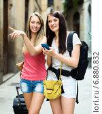 Two smiling girls using smartphone for find a way. Стоковое фото, фотограф Яков Филимонов / Фотобанк Лори