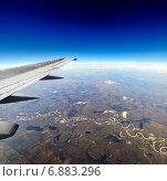 Вид из иллюминатора в полете на синее небо и землю. Стоковое фото, фотограф Антон Довбуш / Фотобанк Лори
