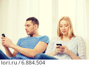 concentrated couple with smartphones at home. Стоковое фото, фотограф Syda Productions / Фотобанк Лори