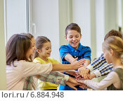 Купить «group of smiling school kids putting hands on top», фото № 6884948, снято 15 ноября 2014 г. (c) Syda Productions / Фотобанк Лори