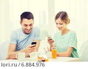 Купить «smiling couple with smartphones reading news», фото № 6884976, снято 9 марта 2014 г. (c) Syda Productions / Фотобанк Лори