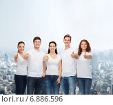 Купить «smiling teenagers in t-shirts showing thumbs up», фото № 6886596, снято 22 июня 2014 г. (c) Syda Productions / Фотобанк Лори