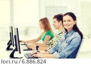 Купить «three smiling students in computer class», фото № 6886824, снято 4 мая 2014 г. (c) Syda Productions / Фотобанк Лори