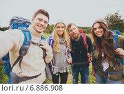 Купить «group of smiling friends with backpacks hiking», фото № 6886908, снято 31 августа 2014 г. (c) Syda Productions / Фотобанк Лори
