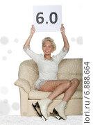 Счастливая фигуристка сидит на диване под снегом и держит над головой лист с оценкой 6.0. Стоковое фото, фотограф Заметалов Андрей / Фотобанк Лори