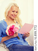smiling woman with card and bouquet of flowers. Стоковое фото, фотограф Syda Productions / Фотобанк Лори