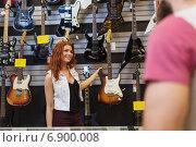 Купить «assistant showing customer guitar at music store», фото № 6900008, снято 11 декабря 2014 г. (c) Syda Productions / Фотобанк Лори