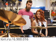 Купить «man and woman with drum kit at music store», фото № 6900016, снято 11 декабря 2014 г. (c) Syda Productions / Фотобанк Лори
