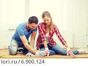 Купить «smiling couple measuring wood flooring», фото № 6900124, снято 26 января 2014 г. (c) Syda Productions / Фотобанк Лори