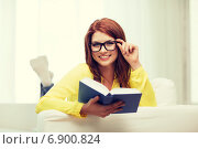 Купить «smiling teenager reading book and sitting on couch», фото № 6900824, снято 19 марта 2014 г. (c) Syda Productions / Фотобанк Лори