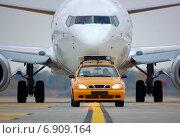 Машина сопровождения ведет пассажирский самолет по аэродрому (2012 год). Редакционное фото, фотограф Антон Довбуш / Фотобанк Лори