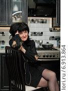 Купить «Печальная женщина с тёмными волосами сидит на стуле в кухне», эксклюзивное фото № 6913864, снято 2 января 2015 г. (c) Игорь Низов / Фотобанк Лори
