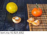 Мандарин, дольки очищенного мандарина и лимон на на темном фоне. Стоковое фото, фотограф Daodazin / Фотобанк Лори