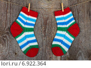 Купить «Разноцветные детские носки висят на веревке на деревянном фоне», фото № 6922364, снято 3 декабря 2014 г. (c) Paleka / Фотобанк Лори