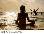 Силуэт женщины, медитирующей на фоне океана. Стоковое фото, фотограф Максим Блинков / Фотобанк Лори