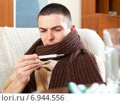 Купить «Sick man looking by thermometer», фото № 6944556, снято 15 октября 2018 г. (c) Яков Филимонов / Фотобанк Лори