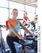 Купить «group of women riding on exercise bike in gym», фото № 6945744, снято 7 июня 2014 г. (c) Syda Productions / Фотобанк Лори