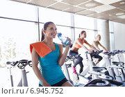Купить «group of women riding on exercise bike in gym», фото № 6945752, снято 7 июня 2014 г. (c) Syda Productions / Фотобанк Лори