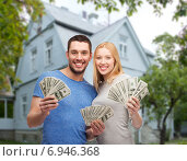 smiling couple showing money over house background. Стоковое фото, фотограф Syda Productions / Фотобанк Лори