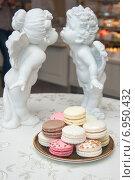 Разноцветные французские пирожные Les Macarons и два ангела на заднем плане. Стоковое фото, фотограф Юлия Костюшина / Фотобанк Лори