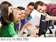 Купить «students looking at computer monitor at school», фото № 6983700, снято 16 июня 2013 г. (c) Syda Productions / Фотобанк Лори