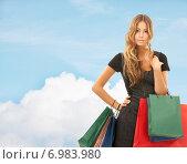 Купить «young happy woman with shopping bags over blue sky», фото № 6983980, снято 14 августа 2010 г. (c) Syda Productions / Фотобанк Лори