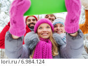 Купить «smiling friends with tablet pc in winter forest», фото № 6984124, снято 29 декабря 2014 г. (c) Syda Productions / Фотобанк Лори