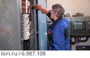 Купить «Пожилой электрик работает с отверткой в руке одетой в резиновую рукавицу в щитке с высоким напряжением», видеоролик № 6987108, снято 10 января 2015 г. (c) Кекяляйнен Андрей / Фотобанк Лори