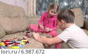 Купить «Мальчик и девочка дошкольного возраста играют в детский конструктор на диване в домашней обстановке», видеоролик № 6987672, снято 12 января 2015 г. (c) Кекяляйнен Андрей / Фотобанк Лори