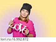 Молодая девушка в розовом свитере и шапке держит в руках декоративную надпись LOVE изолирована на цветном фоне. Стоковое фото, фотограф Екатерина Ярославовна Мостовая / Фотобанк Лори