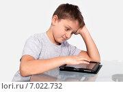 Купить «Мальчик удивленно смотрит на планшетный компьютер», фото № 7022732, снято 4 февраля 2015 г. (c) Дмитрий Боков / Фотобанк Лори