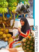 Купить «Мальдивианка в традиционной одежде, торгующая на рынке, ест банан», фото № 7032580, снято 12 февраля 2013 г. (c) Сергей Дубров / Фотобанк Лори