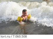 Замерзший мальчик с нарукавниками для плавания сидит в волнах моря. Стоковое фото, фотограф Евгений Пивоваров / Фотобанк Лори