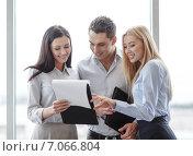 Купить «business team looking at clipboard», фото № 7066804, снято 23 ноября 2013 г. (c) Syda Productions / Фотобанк Лори